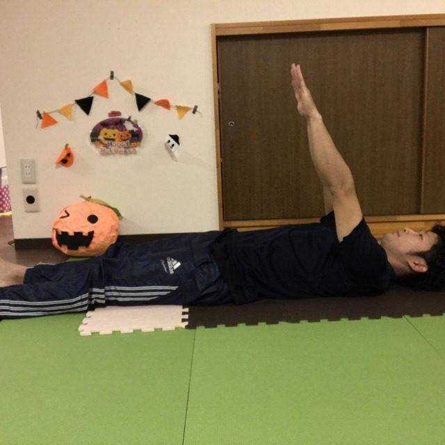 上向きに寝転び両足を伸ばしたまま、両手を天井に向けてまっすぐ上げる。